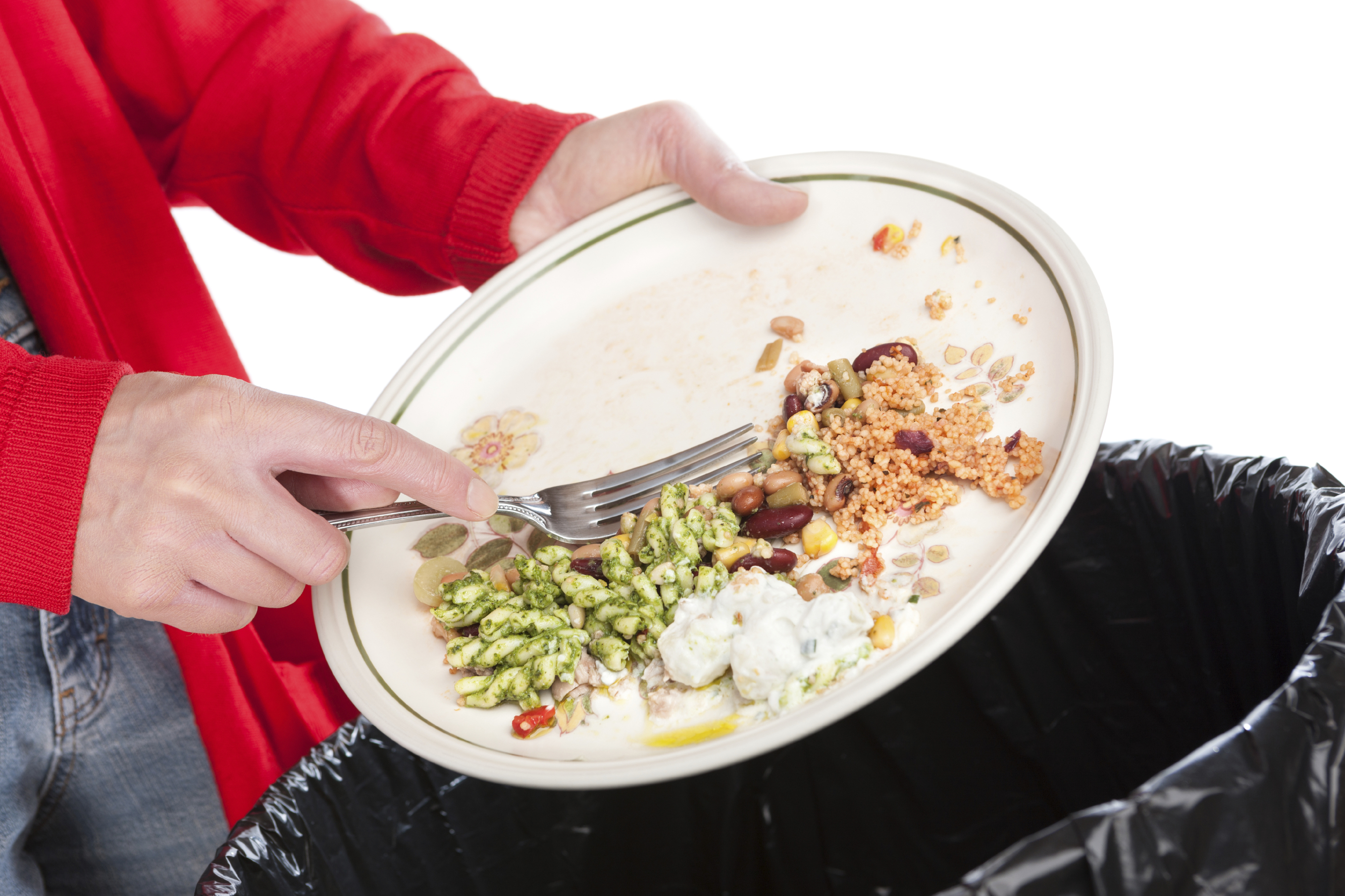 Close-up of a woman sweeping the leftovers from a meal into a garbage bin. The background is pure white.